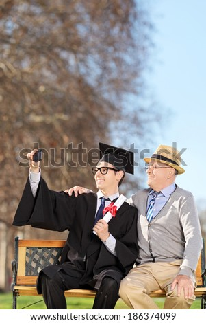 Student and his proud father taking selfie outdoors - stock photo
