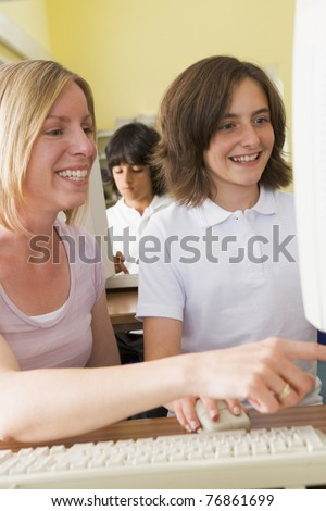 Student and teacher at computer terminal with student in background - stock photo