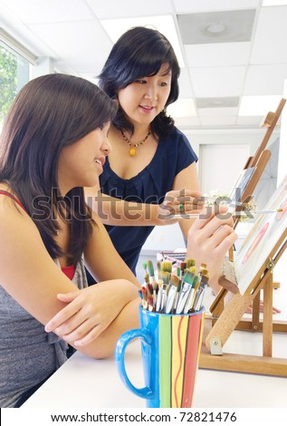Student and teacher during painting lesson - stock photo