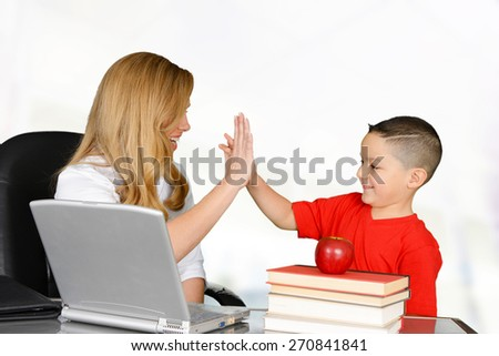 Student and teacher high five in class - stock photo
