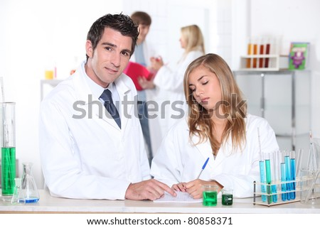 Student and teacher in chemistry class - stock photo