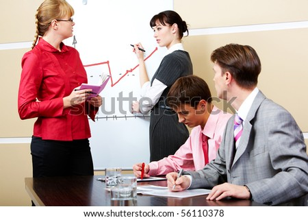 Student and teacher looking at each other at whiteboard with two men staring at them - stock photo