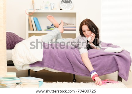 Student apartment - young girl speaking on phone lying on bed