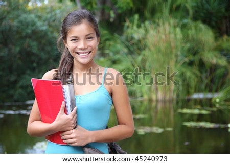 Student. Asian university student holding her books outdoors in the campus park. Cute young mixed race chinese / caucasian woman. - stock photo