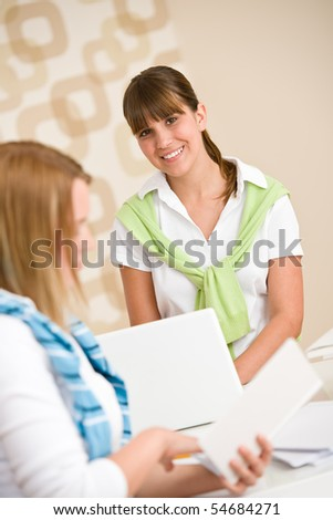 Student at home - two smiling woman with book and laptop study