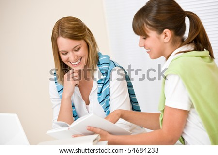 Student at home - two woman with book and laptop study together