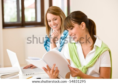 Student at home - two woman with book and laptop study together - stock photo