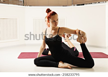 Student behind yoga instructor sitting on a mat - stock photo