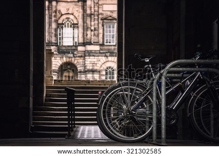 Student bikes on a rack with a view of Edinburgh University in the background. Retro style processing and intentional selective focus on the bikes. - stock photo