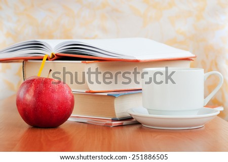 Student books, a cup of coffee and red apple on table. Education concept - stock photo