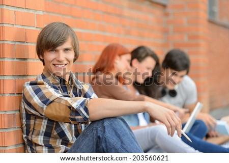 Student boy sitting by brick wall friends smiling in background - stock photo