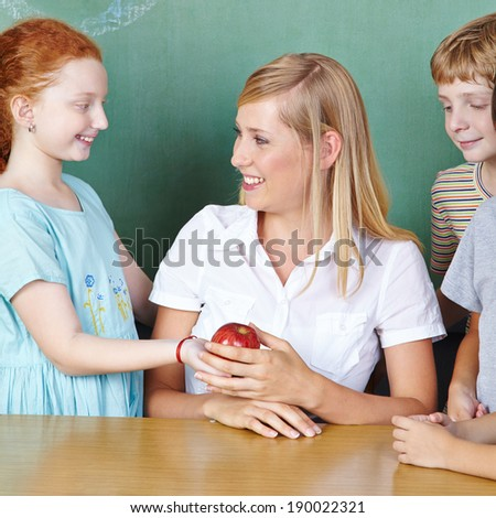 Student bringing teacher an apple in elementary school - stock photo