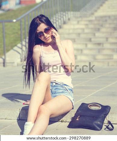 Student brunette sitting on the stairs talking on the phone and fashion style, glamor girl, beautiful woman bright sunny day sitting outside in short shorts wearing glasses with a black bag