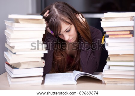 Student buried in books. Studying in the library. Selective focus. - stock photo
