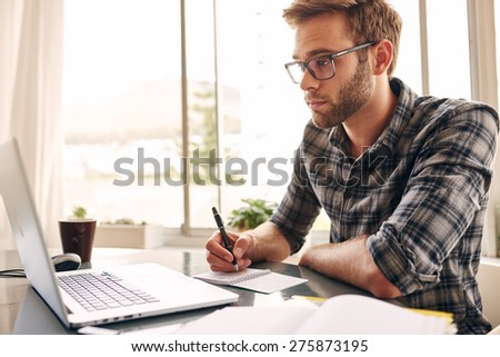 Student busy taking notes down from his new laptop computer while browsing the internet with his morning coffee - stock photo