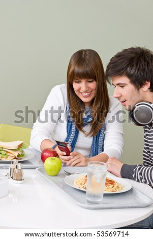 Student cafeteria - teenage couple with mobile phone during lunch break - stock photo