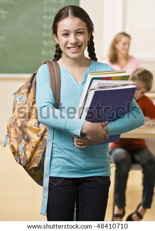Student carrying backpack and books - stock photo