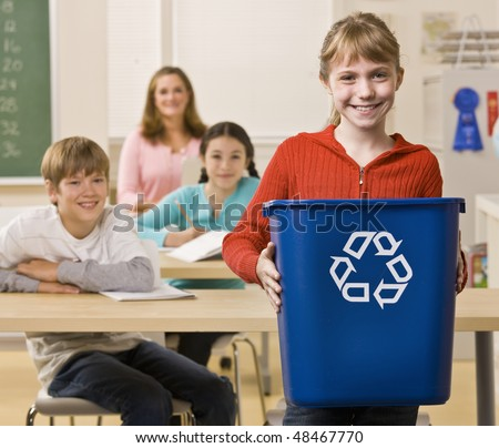 Student carrying recycling bin - stock photo