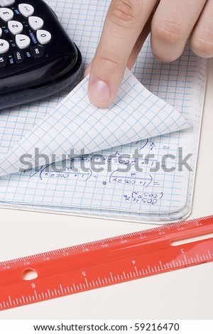 Student checking a problem in a math notebook. - stock photo