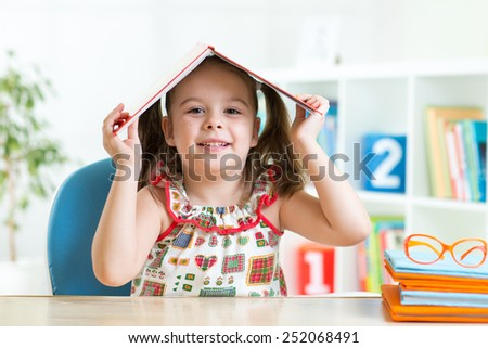 Student child girl with a book over her head - stock photo