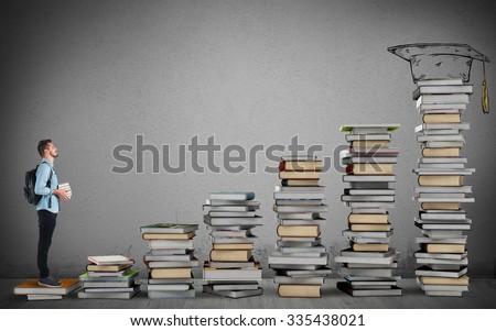 Student climbing a ladder of study books - stock photo