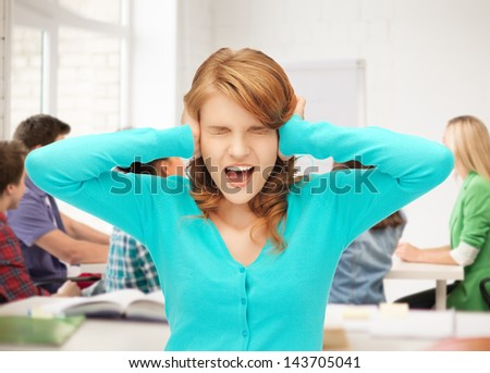 student closing her ears and screaming at school - stock photo