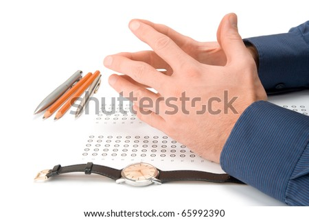Student concentration before complete the examination - hands, blank answer sheet, pencils, pens and watch - stock photo