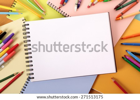 Student desk, art sketch book, pencils, crayons, top view - stock photo