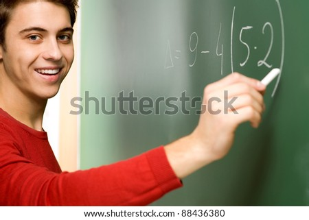 Student Doing Math on Chalkboard - stock photo