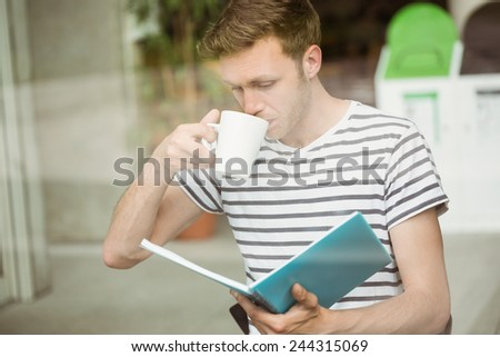 Student drinking a hot drink and holding book in cafe at the university - stock photo