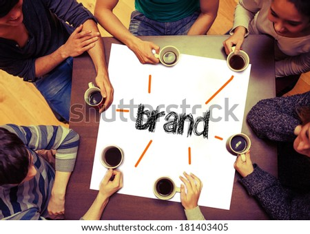Student drinking coffee sitting around page saying the word brand - stock photo