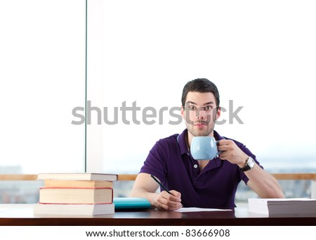 Student drinking coffee whilst studying, looking at camera - stock photo