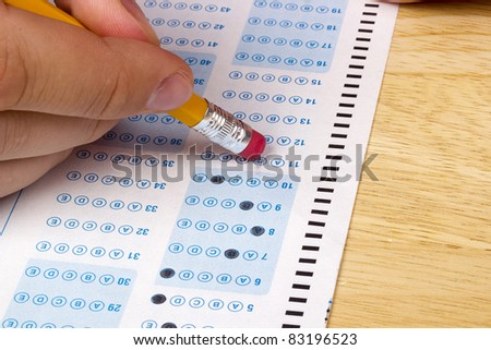 Student erasing a mistake he made on a test. - stock photo