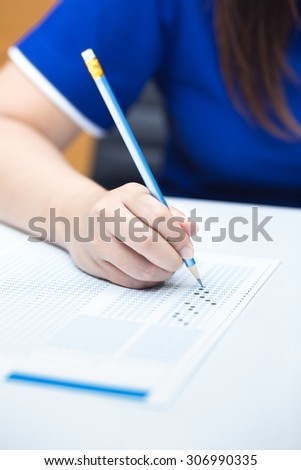 Student filling out answers to blue answer sheet with blue pencil