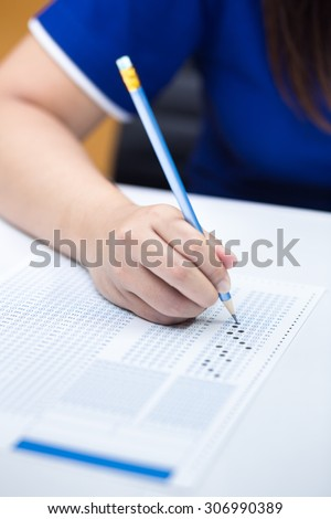 Student filling out answers to blue answer sheet with blue pencil - stock photo