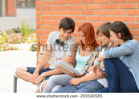 Student friends studying together sitting outside college campus discussing notes - stock photo