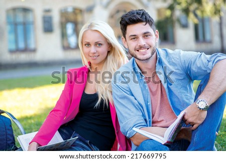 Student friendship. Couple of students sitting on the grass and smiling at the camera while teaching lessons on a break near the university building - stock photo