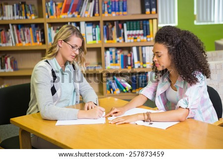Student getting help from tutor in library at the university - stock photo