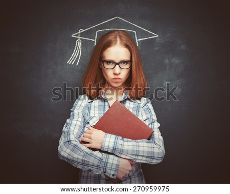 student girl in cap, glasses and a book at the blackboard - stock photo