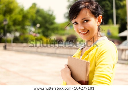 student girl in the city, keeping book, smiling - stock photo