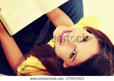 Student girl is smiling and sitting with book on her knee, looking up. - stock photo