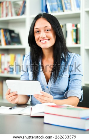Student girl learning in library, using tablet computer - stock photo