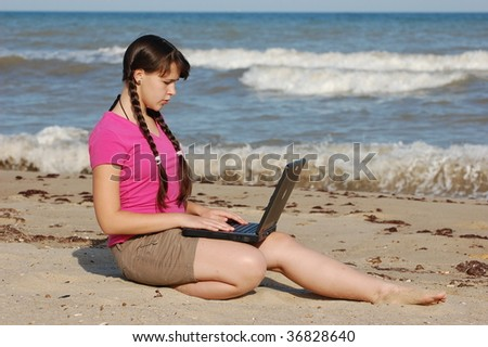 Student girl on the seashore with notebook