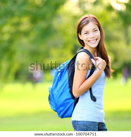 Student girl outside in summer park smiling happy. Asian female college or university student. Mixed race Asian / Caucasian young woman model wearing school bag. - stock photo