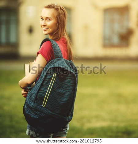 Student girl outside in summer park smiling happy. Caucasian college or university student. Young woman model wearing school bag outdoors in campus.  - stock photo