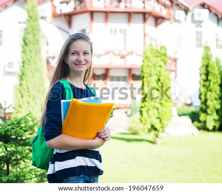 Student girl outside in summer park smiling happy. College or university student young woman with school bag and books. - stock photo