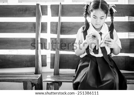 Student girl reading from her book, Black and white - stock photo