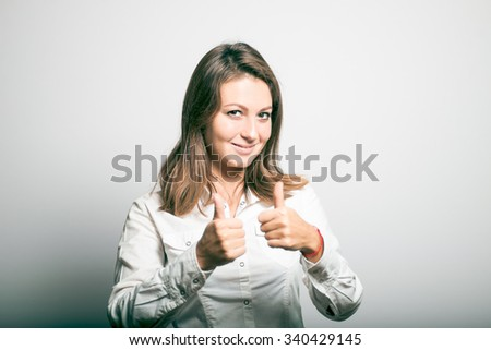 student girl showing thumb up. office manager. studio photo on a gray background - stock photo