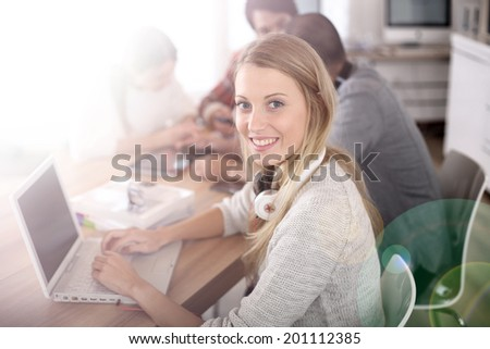 Student girl sitting in class and working on laptop - stock photo