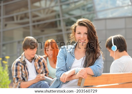 Student girl sitting on bench outside campus with friends sunny - stock photo